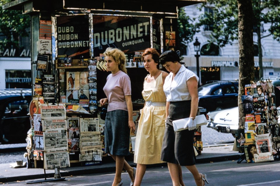 Vintage stock photos of three women walking past a newsstand