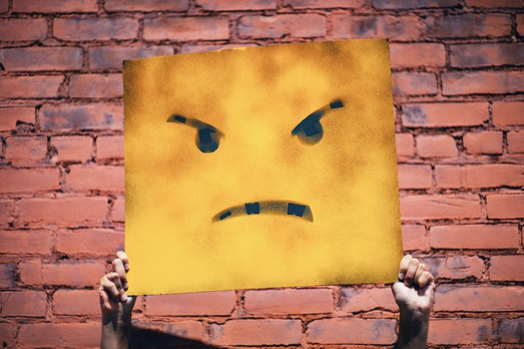 Frustrated emoji on yellow card in from of a genealogy brick wall